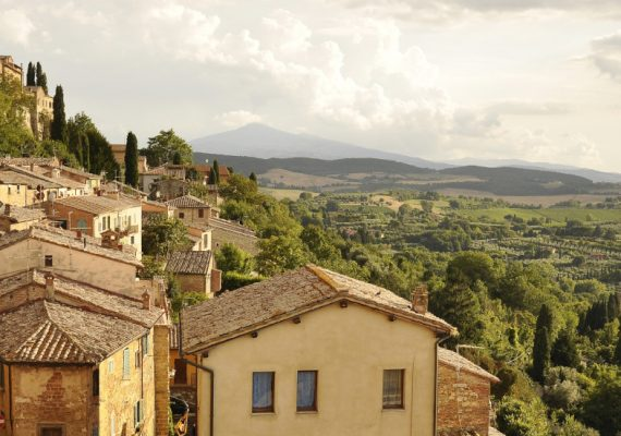 Tuscan landscape with brick buildings overlooking trees
